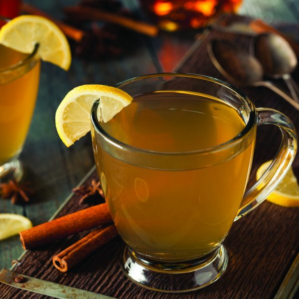 xícara transparente com quentão de vinho e decoração de limão e canela